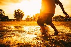 Los niños están jugando al fútbol del fútbol para el ejercicio bajo luz del sol Estilo de la imagen de la silueta y de la películ fotos de archivo libres de regalías