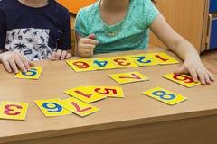 Los niños están jugando Juegos educativos Un niño en guardería Las manos de un niño matemáticas Tarjetas para el desarrollo fotografía de archivo libre de regalías