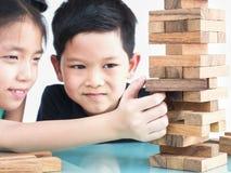 Los niños están jugando a un juego de la torre de los bloques de madera Fotografía de archivo libre de regalías