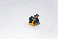 Los niños están patinando en un trineo largo foto de archivo
