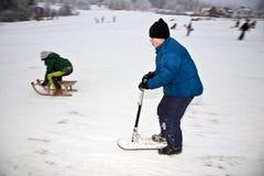 Los niños están patinando en un trineo largo imagen de archivo libre de regalías