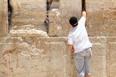 Los niños están poniendo una nota de rogación en un hueco de la pared que se lamenta Fotografía de archivo