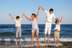 Los niños están saltando en la playa Imagen de archivo libre de regalías