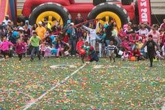 Los niños estrallan sobre el campo de fútbol para la caza del huevo de Pascua de la comunidad Foto de archivo libre de regalías