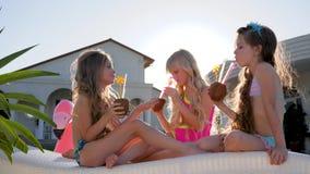 Los niños estropeados con los cócteles coloreados en ocioso del sol, niñas en traje de baño se divierten cerca del chalet en el c metrajes