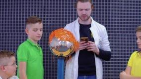 Los niños exploran el generador del graaff de van de almacen de video