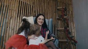 Los niños felices abrazan a su madre cariñosa que celebre el libro en su mano y se siente en la silla al lado de la pared almacen de video