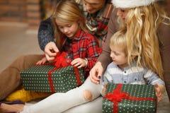 Los niños felices abren los regalos de la Navidad Imágenes de archivo libres de regalías