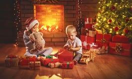Los niños felices abren los regalos de la Navidad en la noche en el árbol de navidad Imagenes de archivo