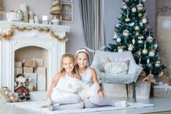 Los niños felices acercan al árbol de Navidad Fotografía de archivo