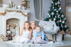 Los niños felices acercan al árbol de Navidad Imagen de archivo libre de regalías