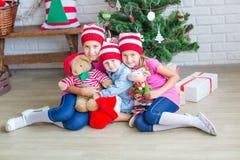 Los niños felices acercan al árbol de Navidad Foto de archivo libre de regalías