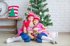 Los niños felices acercan al árbol de Navidad Imagenes de archivo
