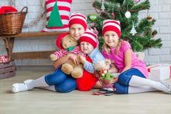 Los niños felices acercan al árbol de Navidad Imagen de archivo