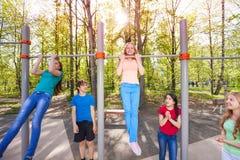 Los niños felices chinning para arriba en el patio Imágenes de archivo libres de regalías