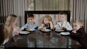 Los niños felices comen la pizza en el restaurante almacen de metraje de vídeo