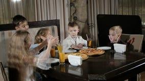 Los niños felices comen la pizza en el restaurante metrajes