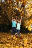 Los niños felices con caída colorida se van al aire libre Foto de archivo