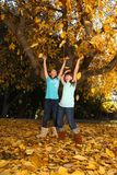 Los niños felices con caída colorida se van al aire libre Imágenes de archivo libres de regalías