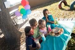 Los niños felices con la cara pintan tener comida y bebidas en el parque Foto de archivo libre de regalías