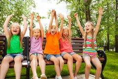 Los niños felices con los brazos y se sientan en fila en banco Fotos de archivo