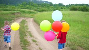 Los niños felices corren en un camino forestal con los globos Celebración del cumpleaños en el parque Risa y alegría de niños metrajes