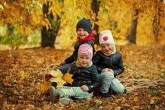 Los niños felices de los amigos del retrato tres en otoño parquean - el niño, el leisute y la amistad Fotos de archivo libres de regalías