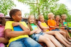 Los niños felices de la escuela en banco se sientan en fila juntos Fotografía de archivo