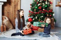 Los niños felices desempaquetan los regalos para la Navidad El concepto de Cristo Fotografía de archivo libre de regalías