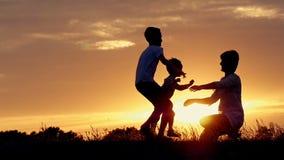 Los niños felices el funcionamiento de los muchachos a su madre y la abrazan