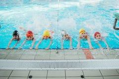 Los niños felices embroman al grupo en la clase de la piscina que aprende nadar foto de archivo