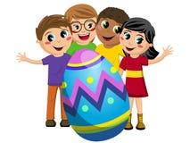 Los niños felices embroman alrededor del huevo de Pascua adornado grande Foto de archivo