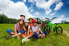 Los niños felices en cascos se sientan en hierba y abrazo foto de archivo