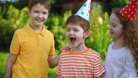 Los niños felices en casquillos del festival felicitan a su amigo en cumpleaños almacen de video