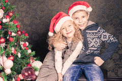 Los niños felices en el día de fiesta de la Navidad cerca adornaron el árbol de navidad Fotos de archivo libres de regalías
