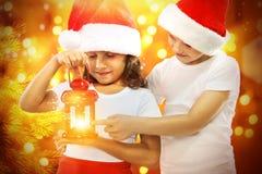Los niños felices en el sombrero de Papá Noel miran la Navidad roja Fotos de archivo libres de regalías