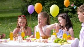 Los niños felices en fiesta de cumpleaños en el verano cultivan un huerto metrajes