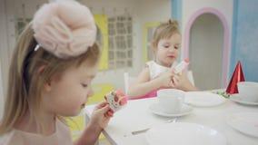 Los niños felices están comiendo el helado en fiesta de cumpleaños por la tabla almacen de video