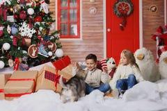 Los niños felices están mintiendo en piso cerca del árbol de navidad y están abrazando el perro Están mirando la cámara y la sonr Imagen de archivo