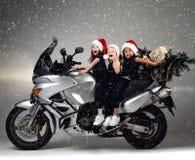 Los niños felices jovenes de las muchachas montan una bici de la motocicleta en el sombrero y el árbol de navidad de santa Fotografía de archivo