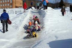 Los niños felices montan de la colina congelada al fin de semana Fotos de archivo libres de regalías