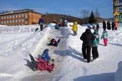 Los niños felices montan de la colina congelada al fin de semana en el pueblo Imagen de archivo