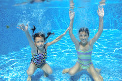 Los niños felices nadan en piscina bajo el agua, las muchachas que nadan Fotografía de archivo libre de regalías