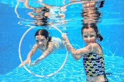 Los niños felices nadan en piscina bajo el agua, las muchachas que nadan Imágenes de archivo libres de regalías