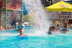 Los niños felices que se divierten en la piscina del parque del agua con salpican del agua Fotografía de archivo