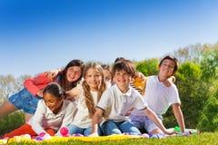 Los niños felices que se sientan en el césped en verano parquean Imagen de archivo libre de regalías