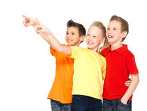 Los niños felices señalan por el dedo en algo lejos. Fotos de archivo libres de regalías