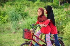 Los niños femeninos de un malay joven montan una bicicleta en su ciudad natal Vea un fondo del pueblo rural malayo Imagenes de archivo
