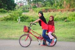 Los niños femeninos de un malay joven montan una bicicleta en su ciudad natal Vea un fondo del pueblo rural malayo Fotografía de archivo libre de regalías