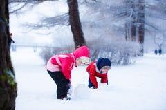 Los niños forman el muñeco de nieve Fotografía de archivo